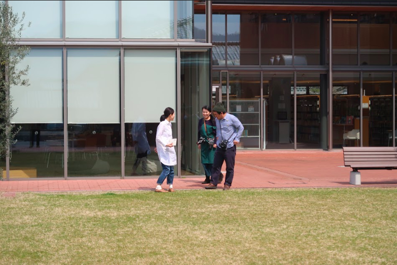 芝生のまえで打ち合わせする濱田英明さん(5) ©キハラ株式会社